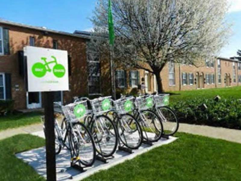 Bike Share stand with sign and 5 bicycles